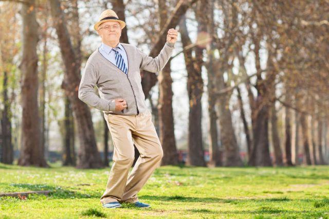 30087286 - senior man playing air guitar in the park