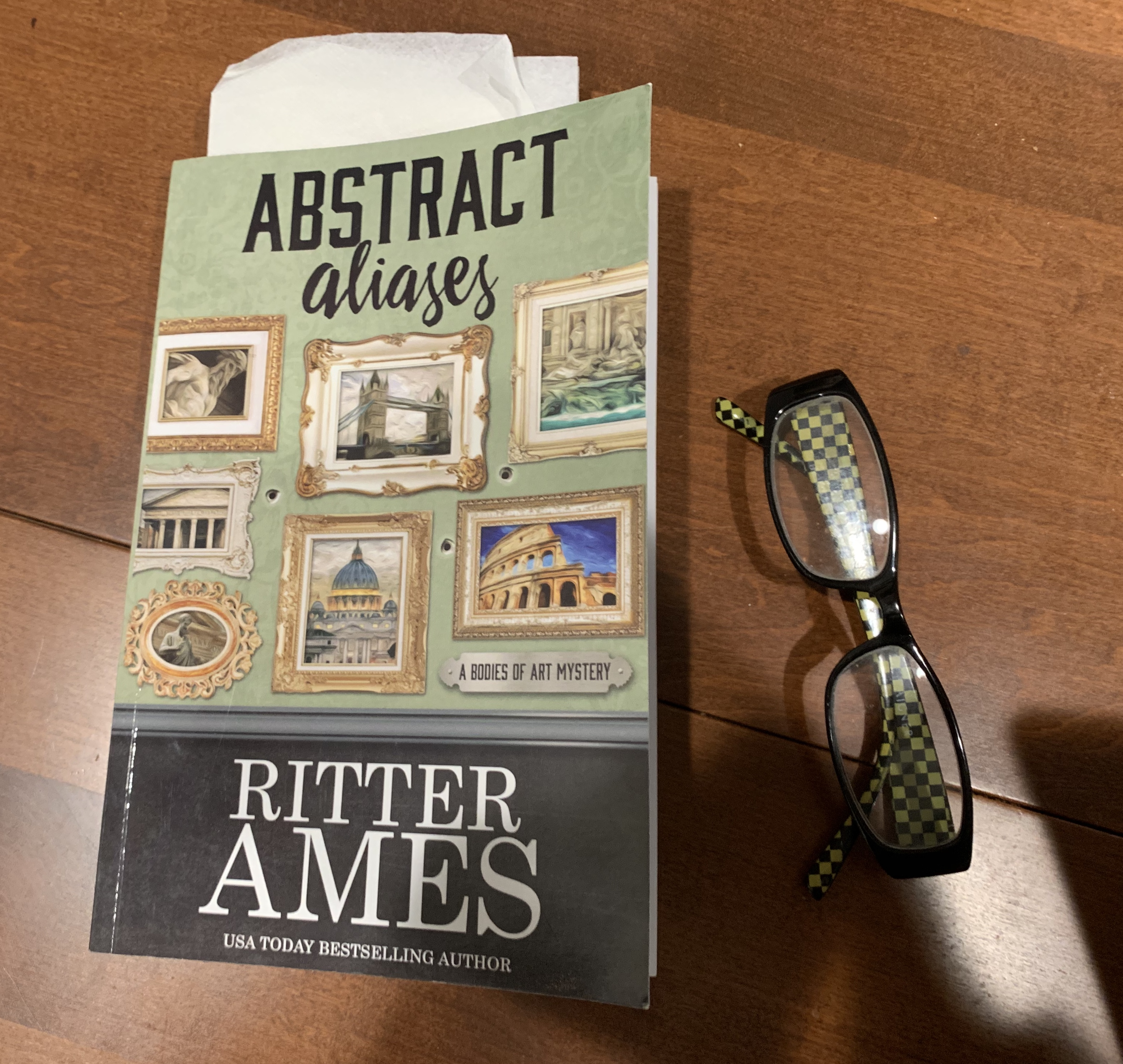 My paperback copy of Astract Aliases by Ritter Ames  Ritter's site page with links to all available vendors & versions ( paper, hard cover, ebook - Amazon, Kobo, B&N, Apple, Google )  https://ritterames.com/books/abstract-aliases/